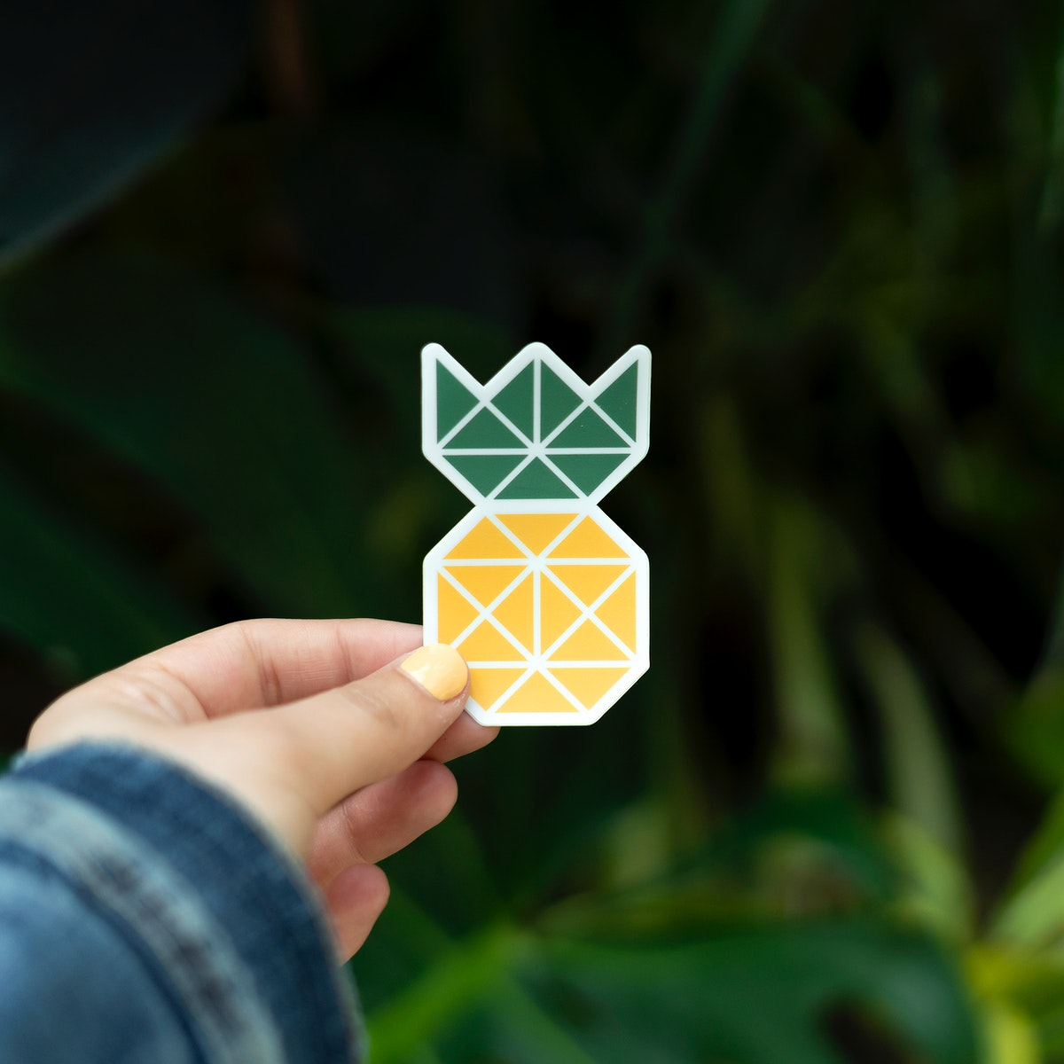 Pineapple sticker held up outdoors