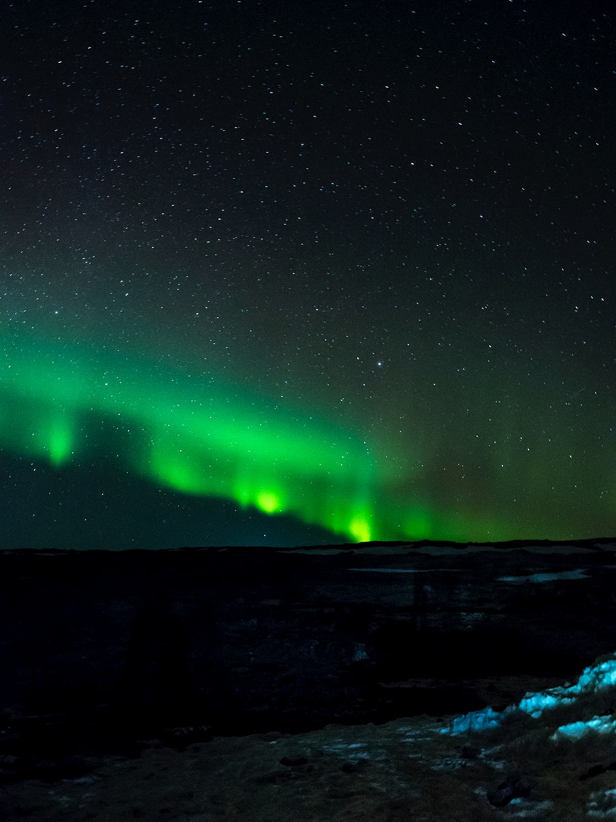 Hills covered with snow and northern lights