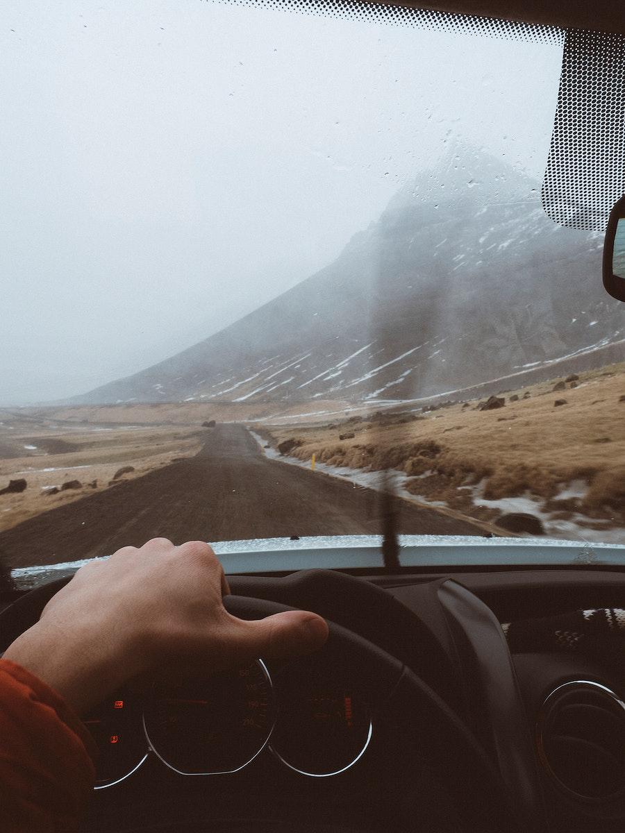 Man driving a car through rural Iceland