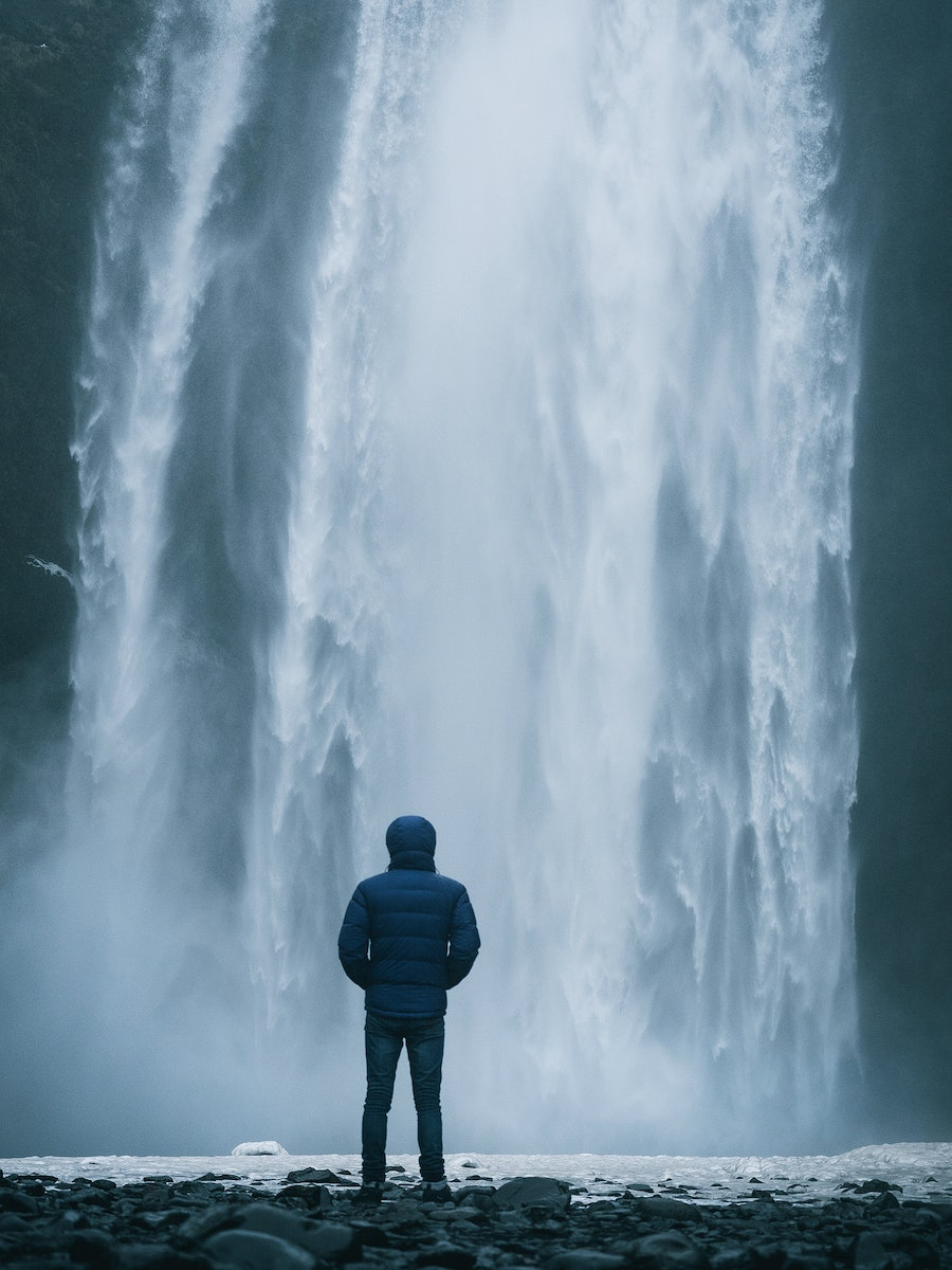 Man enjoying a view of Skógafoss waterfall in Iceland