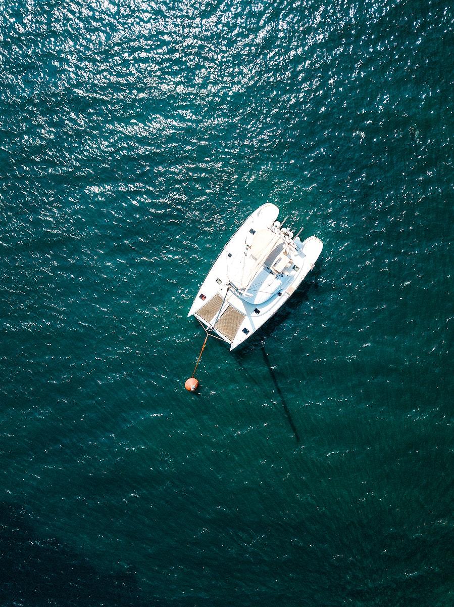 Aerial view of catamaran cruise on Aegean sea, Oía Santorini, Greece