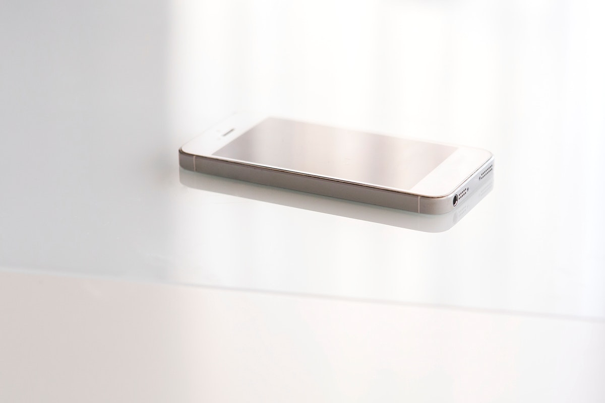 Smartphone on a white desk. Visit Kaboompics for more free images.