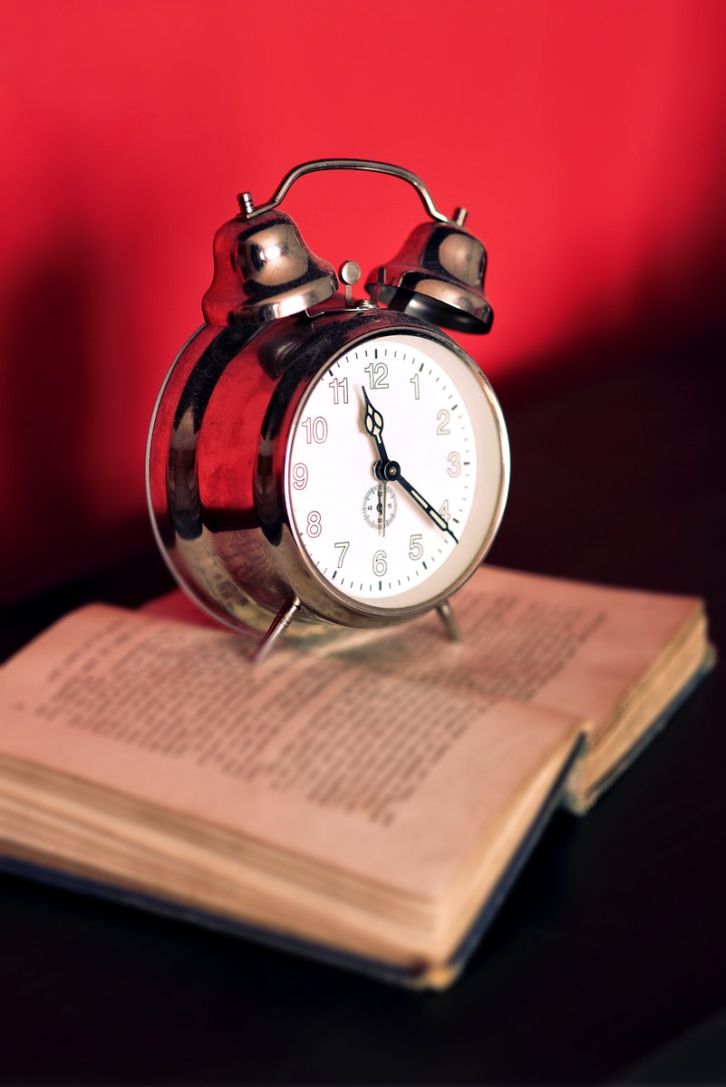 Alarm clock on a book. Visit Kaboompics for more free images.