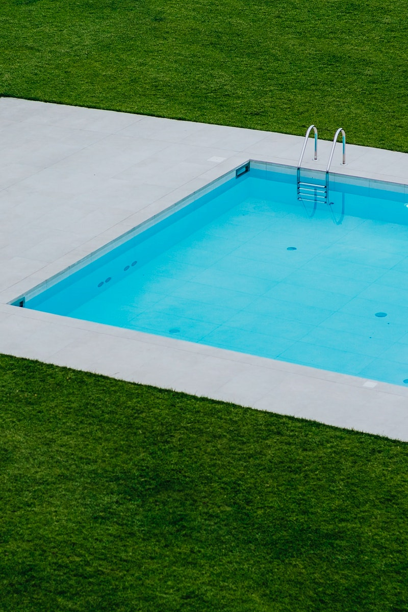 Swimming pool surrounded by green grass. Visit Kaboompics for more free images.