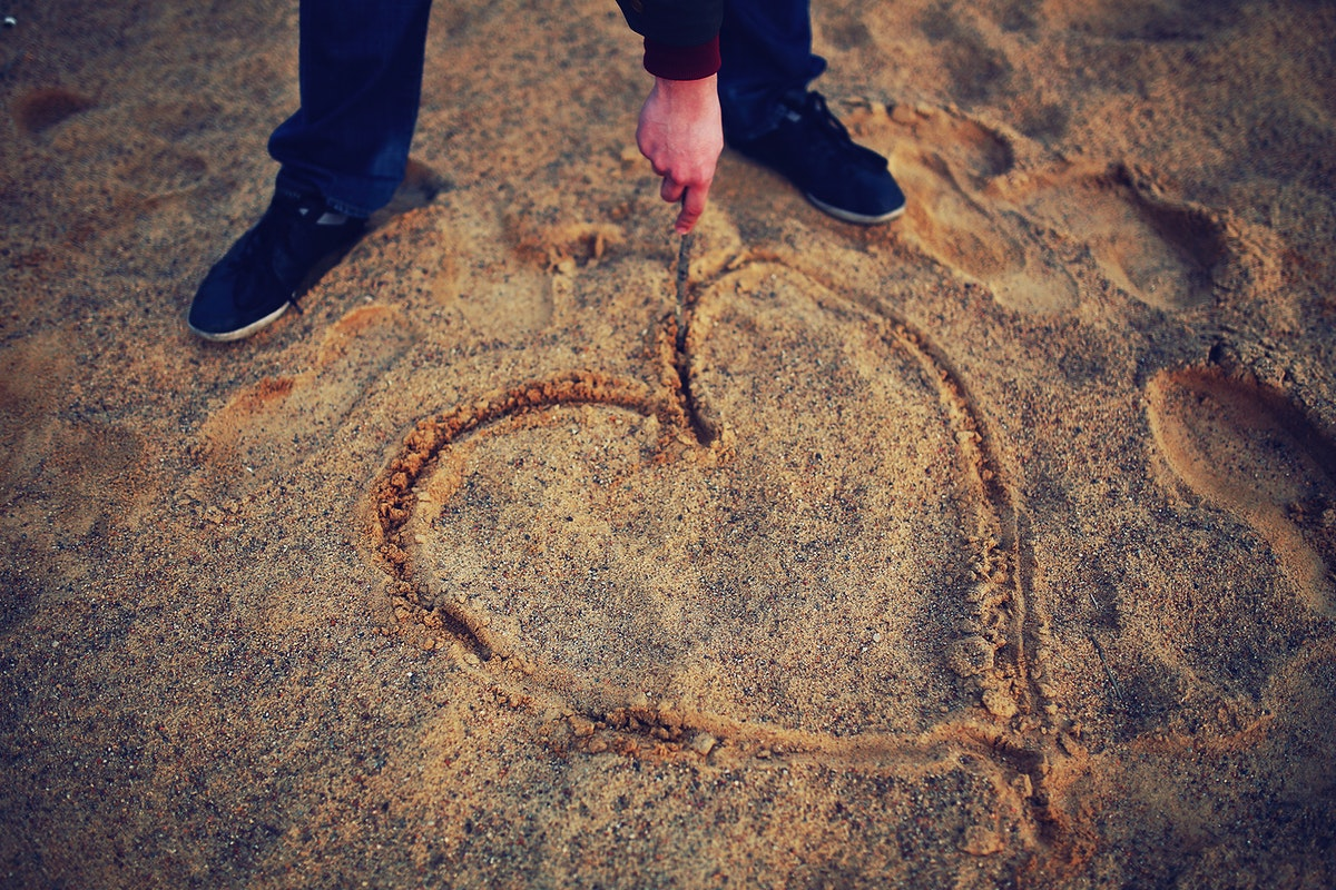 Man drawing a heart in the sand. Visit Kaboompics for more free images.
