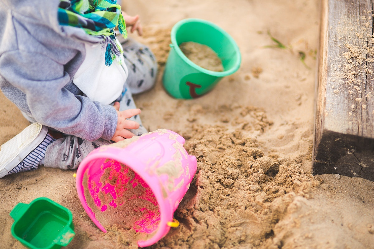 Toddler playing with sand. Visit Kaboompics for more free images.