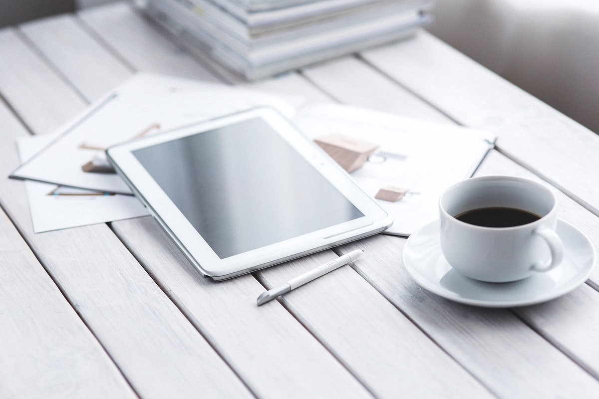 Tablet and a coffee cup on a table. Visit Kaboompics for more free images.