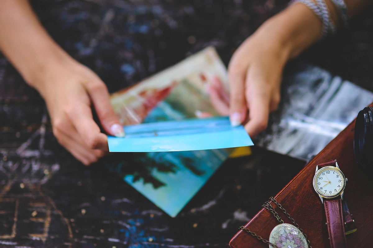 Woman looking at postcards. Visit Kaboompics for more free images.