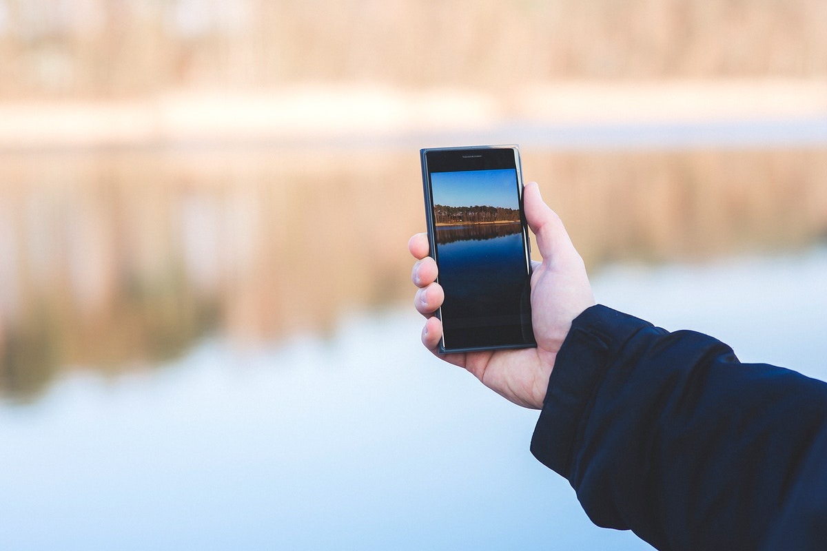 Man taking a photo of a lake. Visit Kaboompics for more free images.