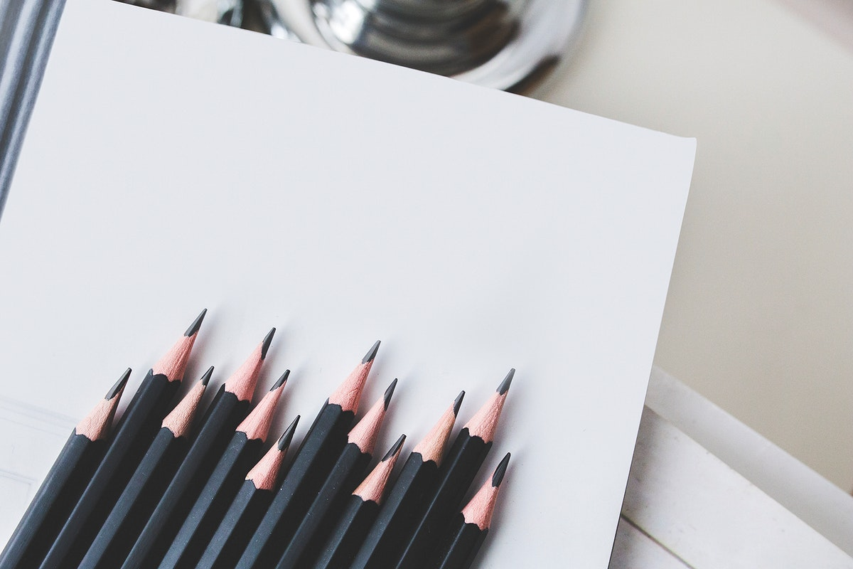 Flat lay of pencils on blank paper. Visit Kaboompics for more free images.