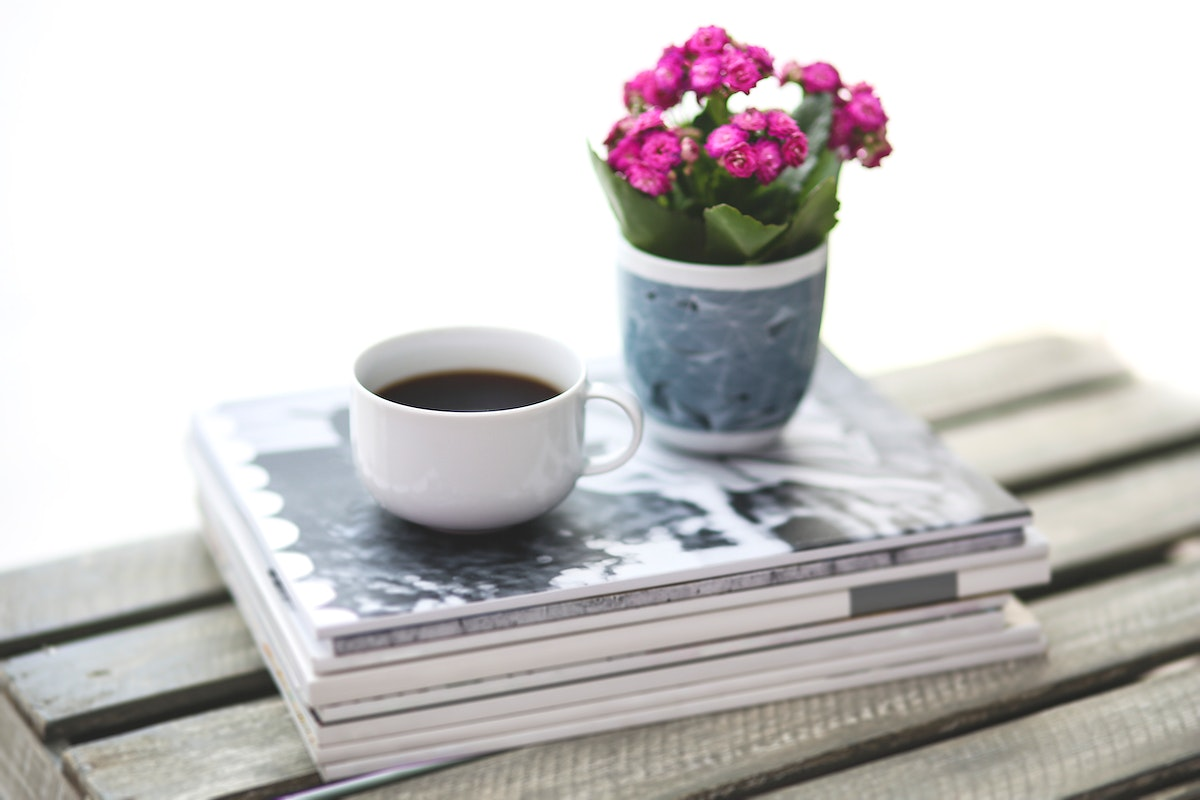 Cup of coffee and flowers on a table. Visit Kaboompics for more free images.