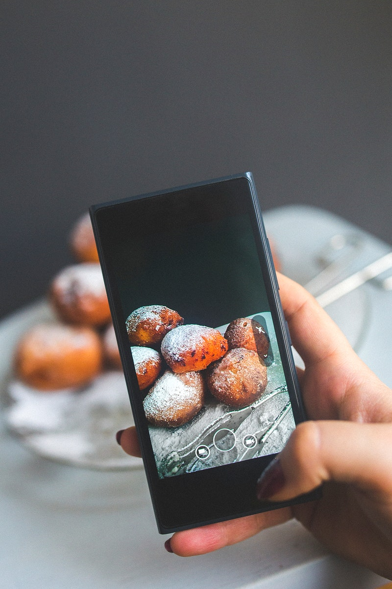 Woman taking a photo of pastries. Visit Kaboompics for more free images.