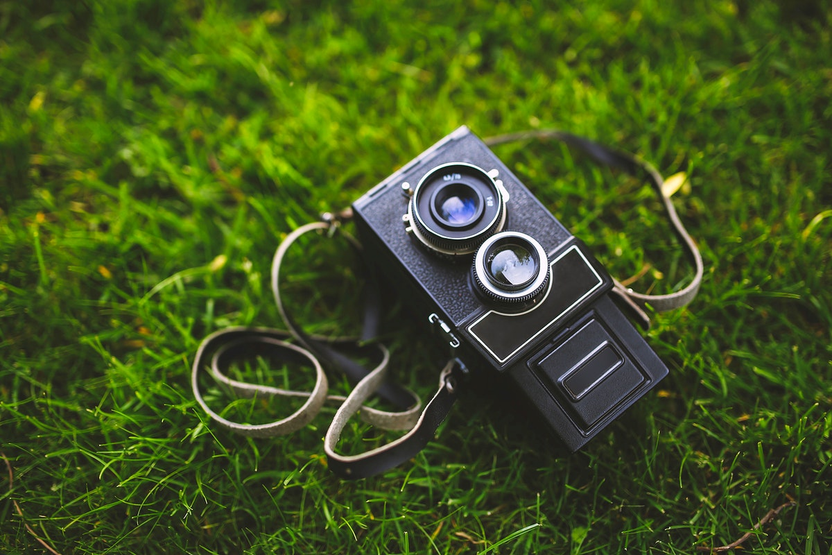 Vintage analog film camera on a grass. Visit Kaboompics for more free images.