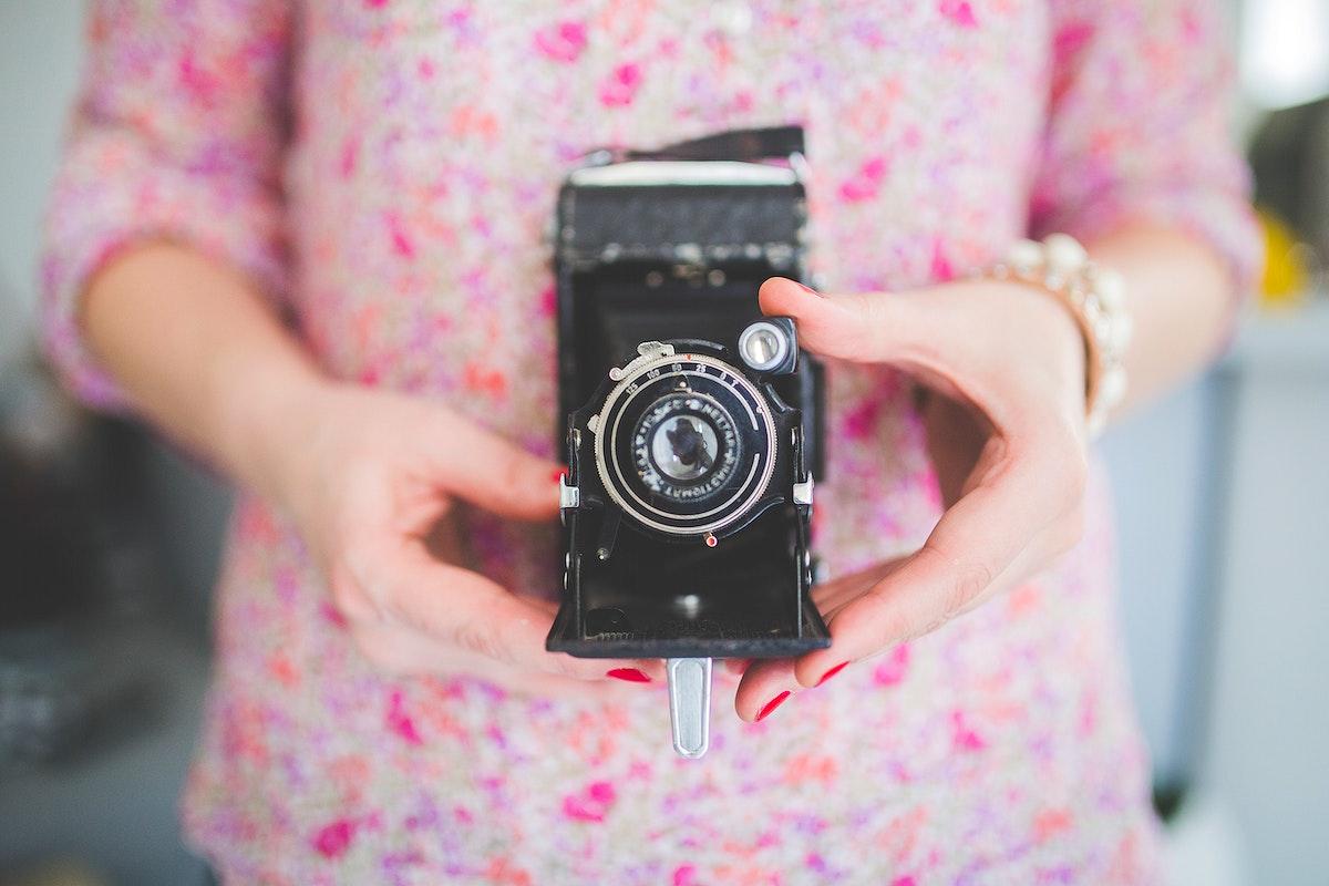 Woman holding vintage analog film camera. Visit Kaboompics for more free images.