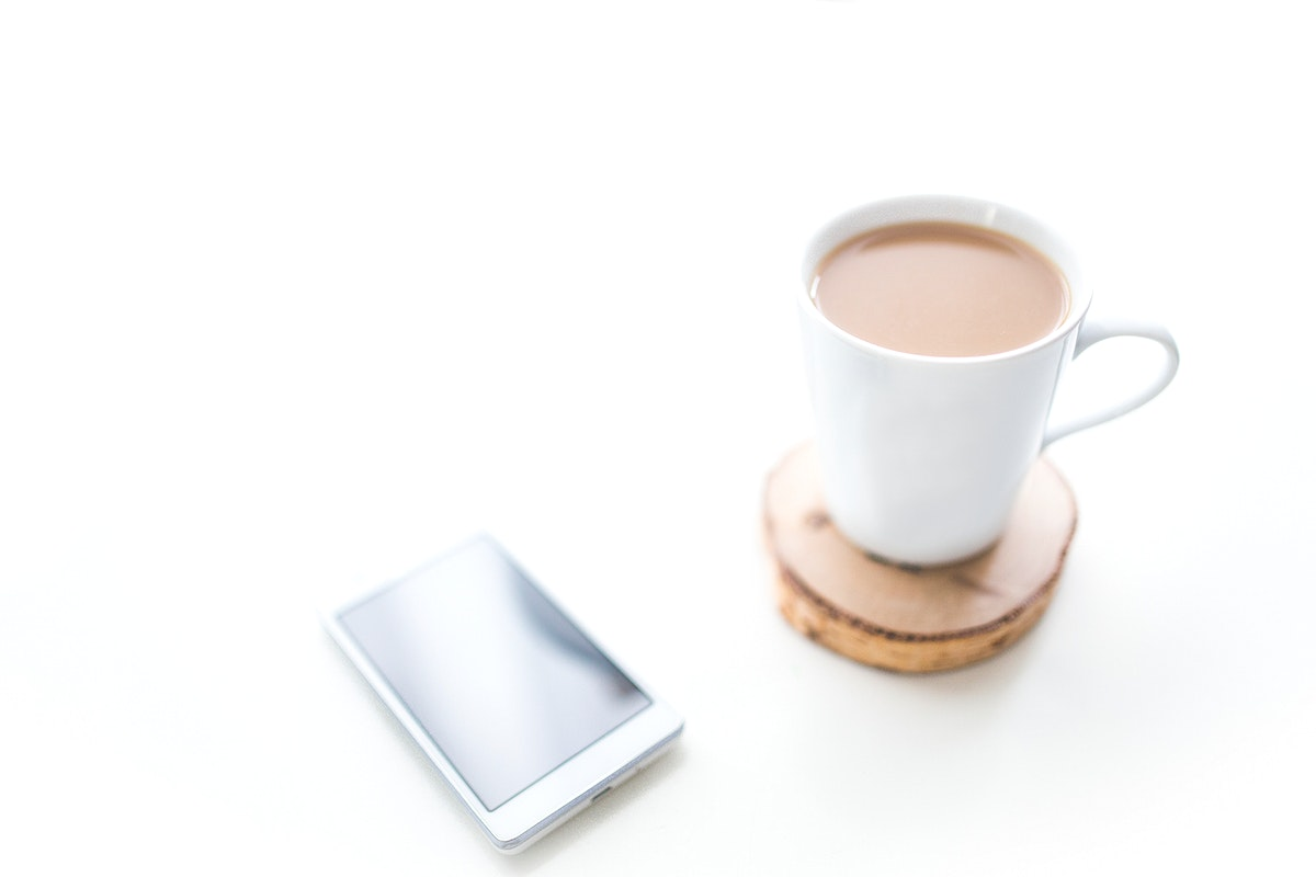 Cup of coffee and a phone. Visit Kaboompics for more free images.