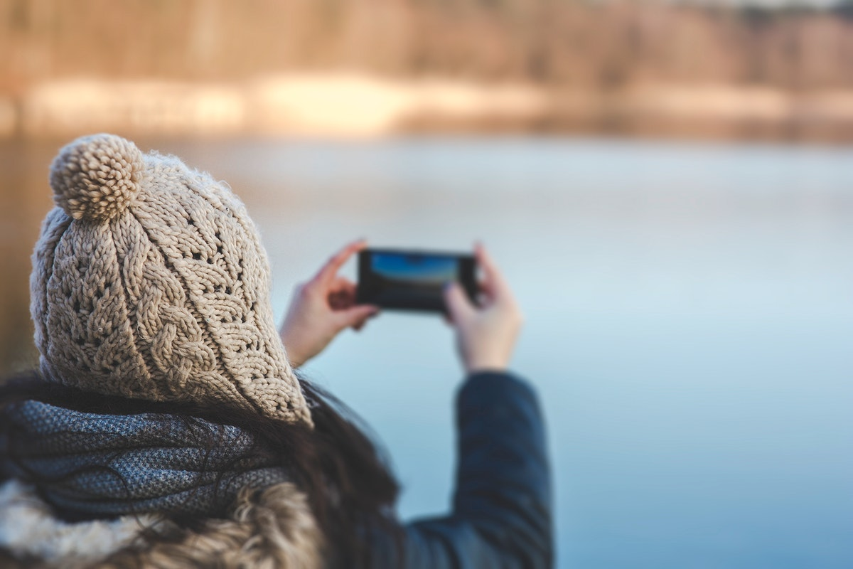 Woman taking a photo of a lake. Visit Kaboompics for more free images.