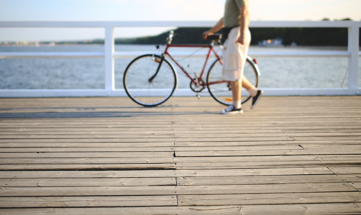 Man walking with a bicycle. Visit Kaboompics for more free images.