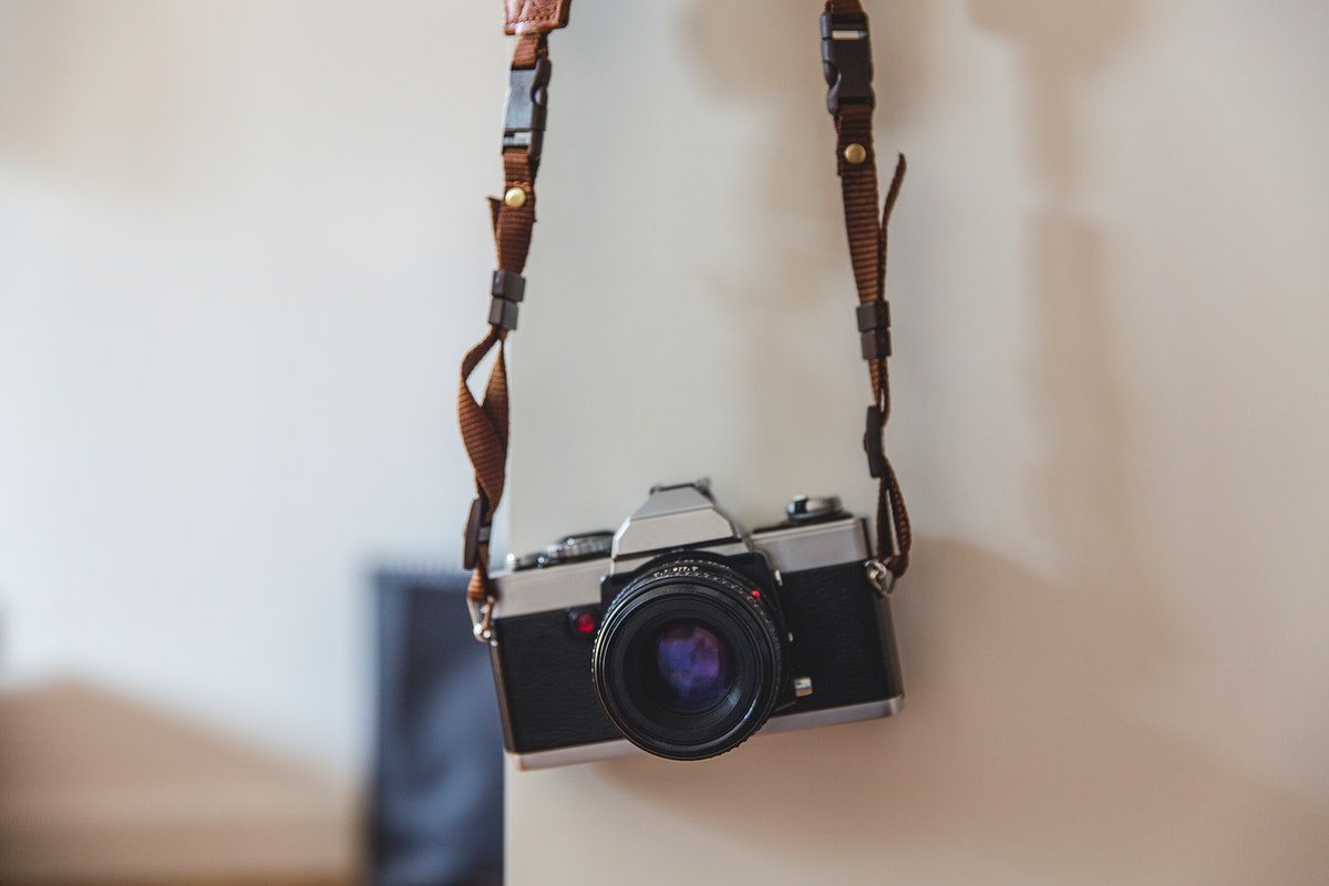 Vintage analog 35mm film camera hanging on a wall