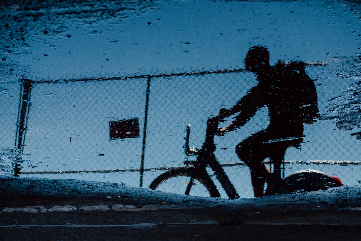 Reflection of a cyclist in a puddle