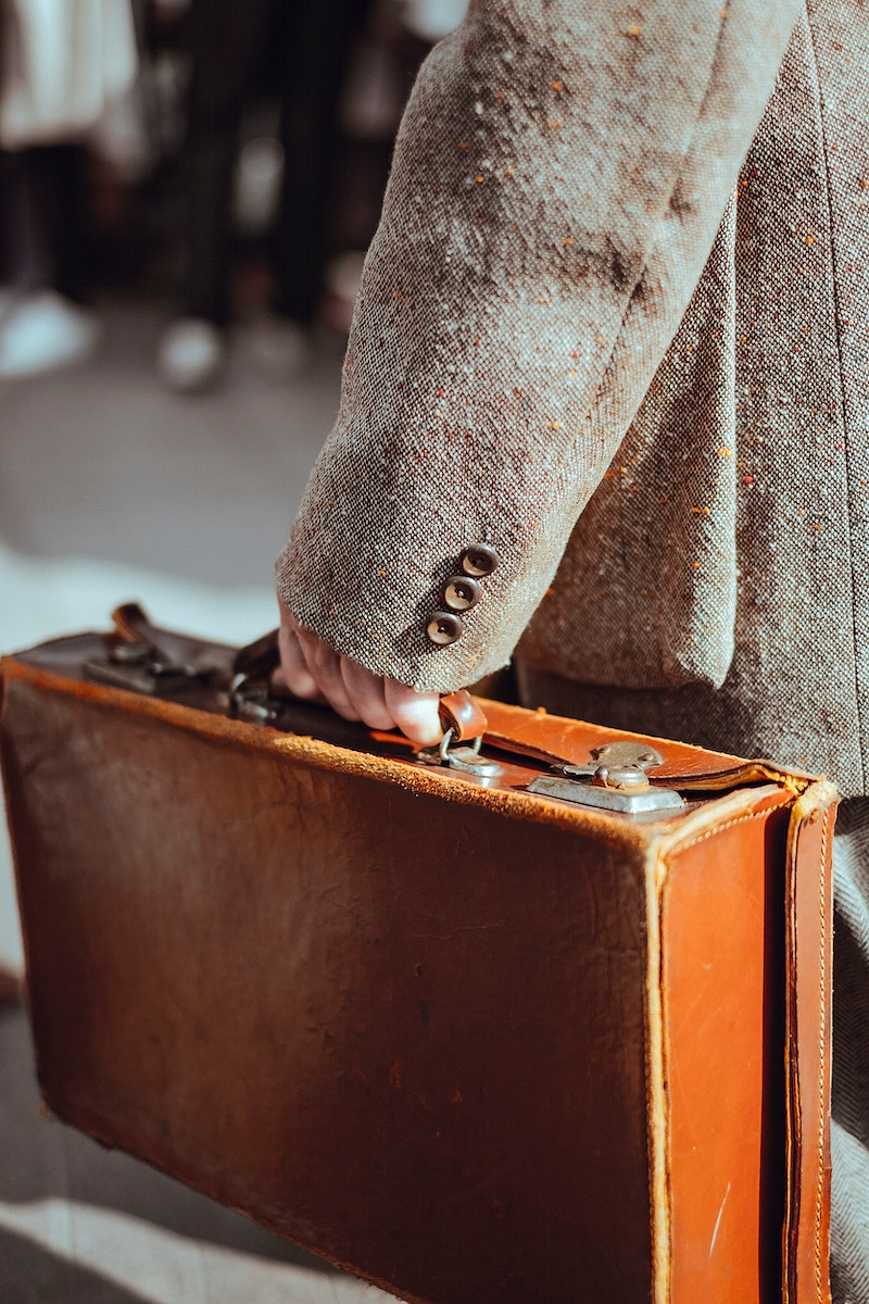 Mature man carrying a vintage leather briefcase