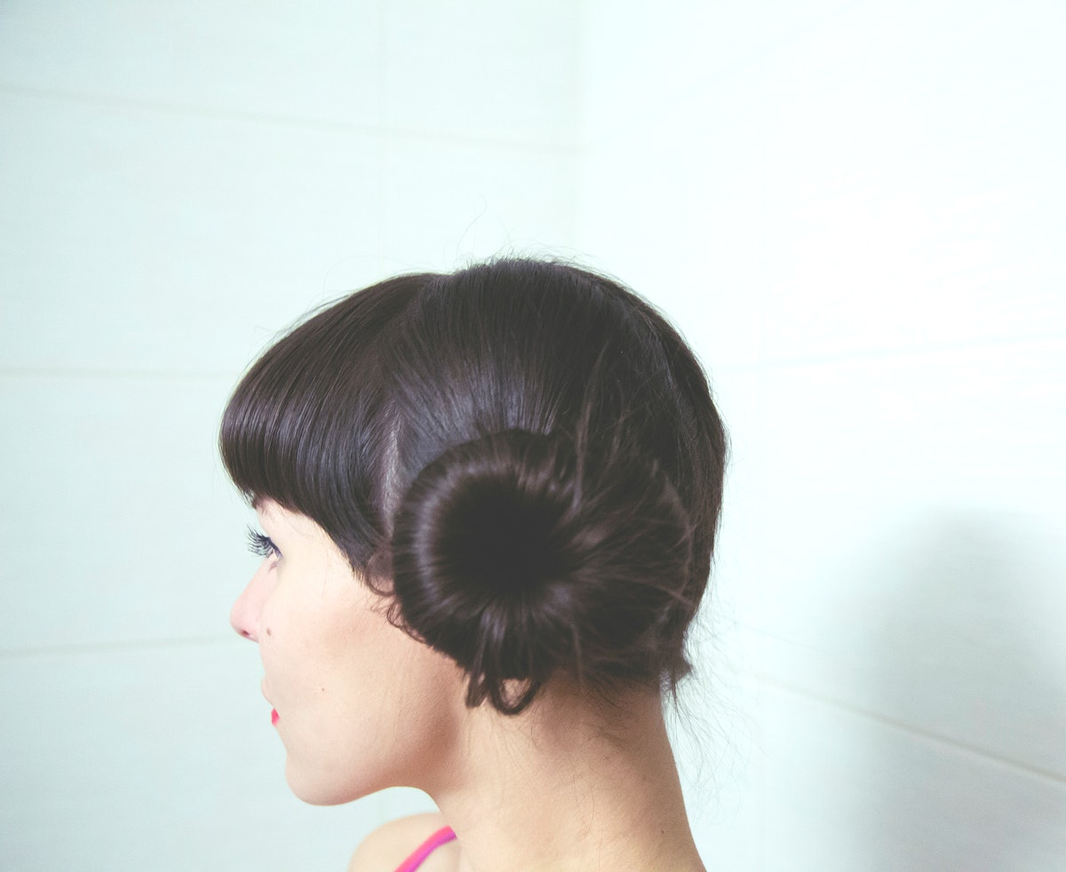 Profile of a woman with donut bun hairstyle