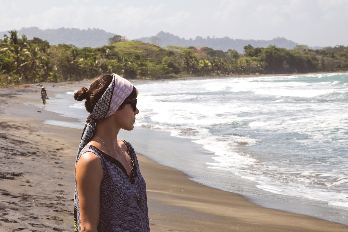 Woman with a head scarf by the beach