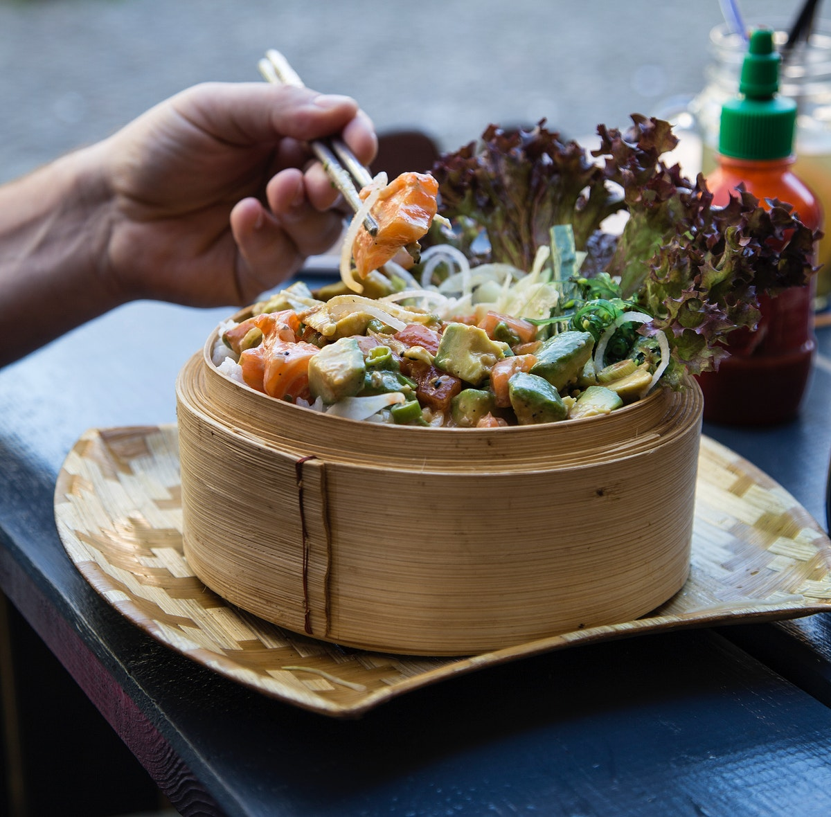 Eating a colorful Asian salad in a bamboo steamer