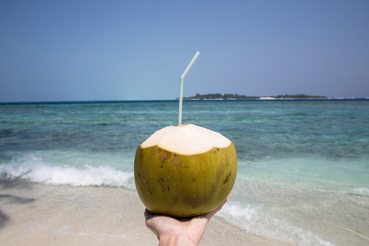 Woman holding a coconut at the beach