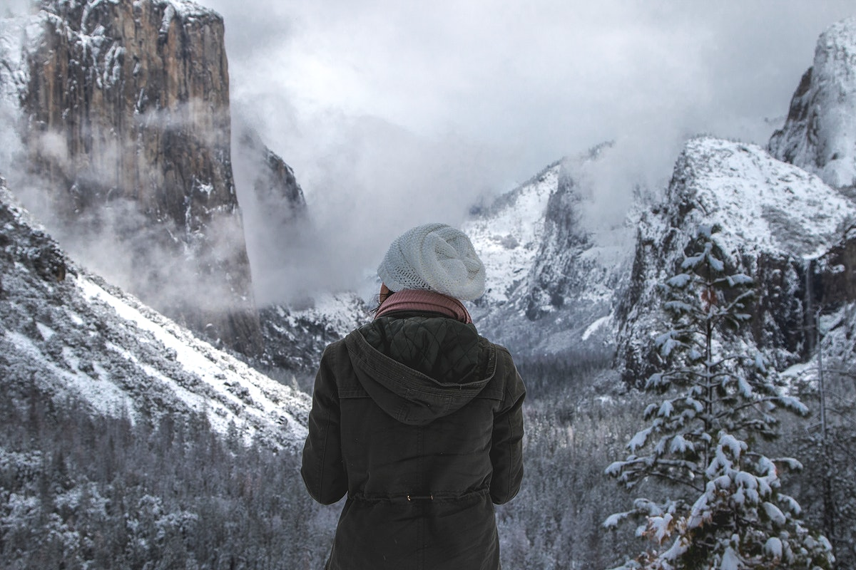 Woman looking at the mountain peaks in Yosemite Valley, USA