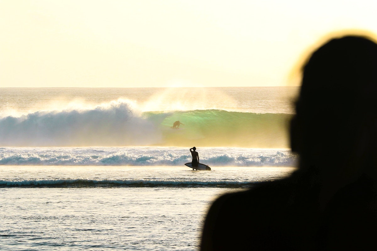Surfer on a deserted beach in Indonesia