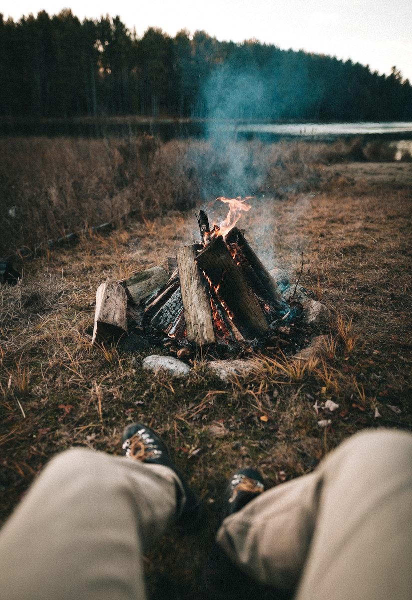 Man enjoying the bonfire by a lake