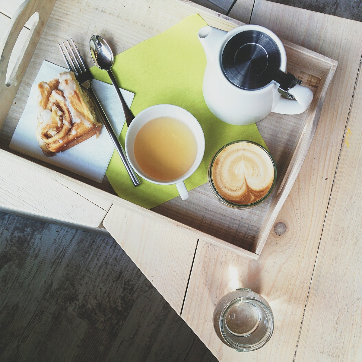 Cappuccino, tea,  and cinnamon roll