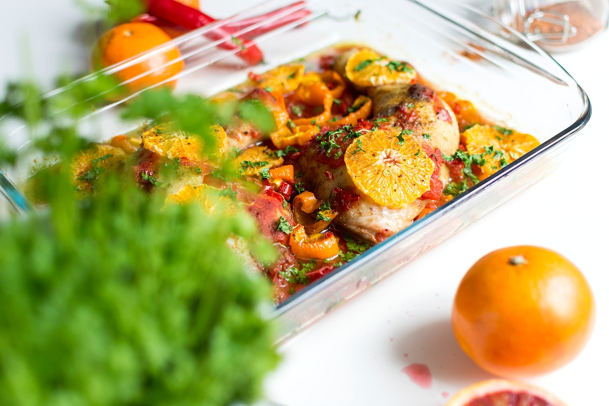 Chicken thighs with tomatoes, peppers, and oranges.