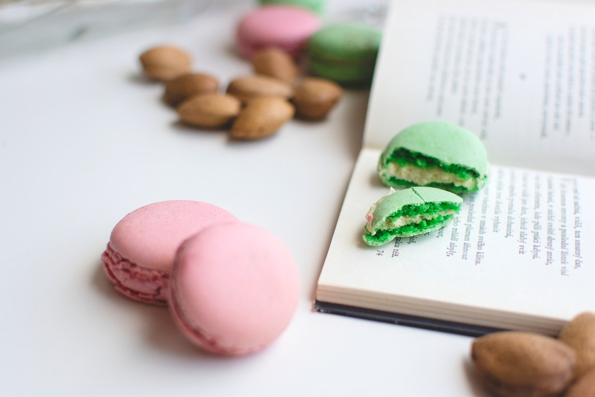 Pink and green macaroons and a book on the table