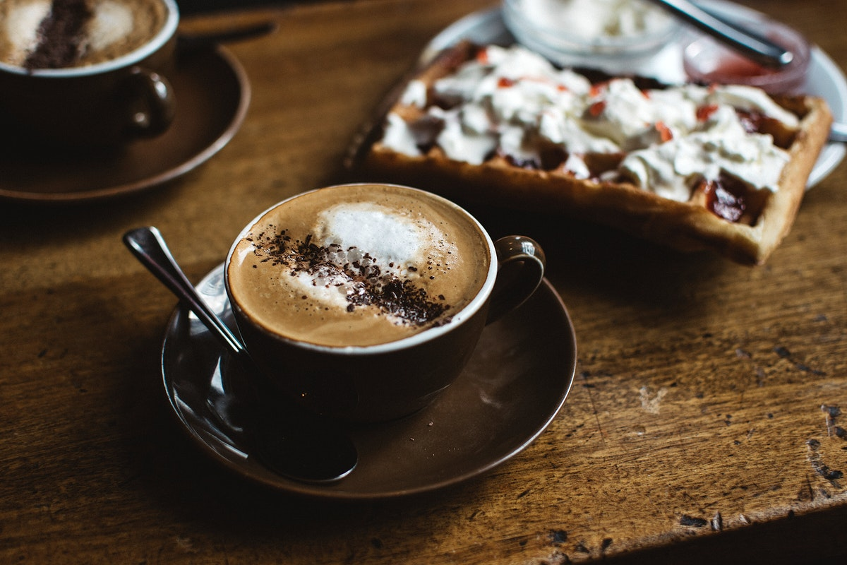 Hot cappuccino with chocolate powder and a waffle
