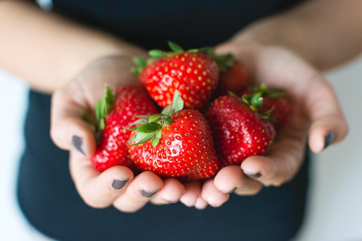 Woman carrying fresh strawberries