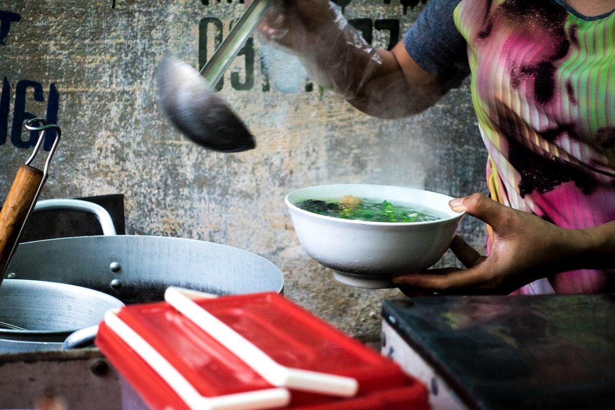 A seller preparing Pho, a Vietnamese noodle soup