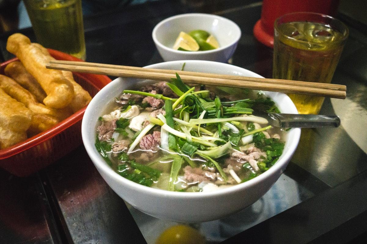 Eating Pho Bo, a Vietnamese noodle soup