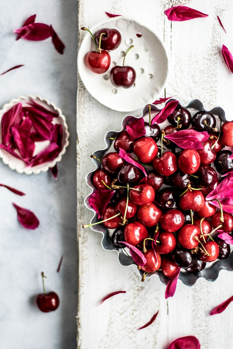 Tray filled with fresh cherries and flower petals. Visit Monika Grabkowska to see more of her food photography.