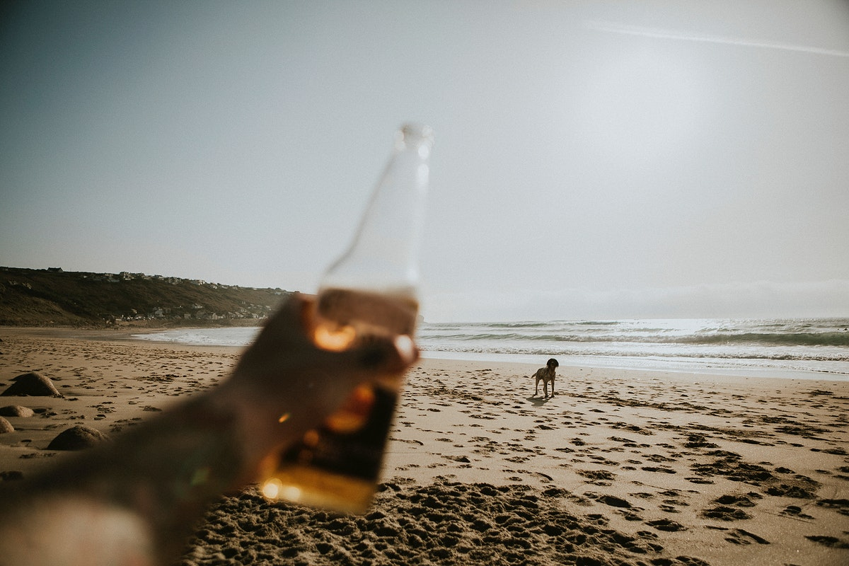 Holding a beer bottle on the beach