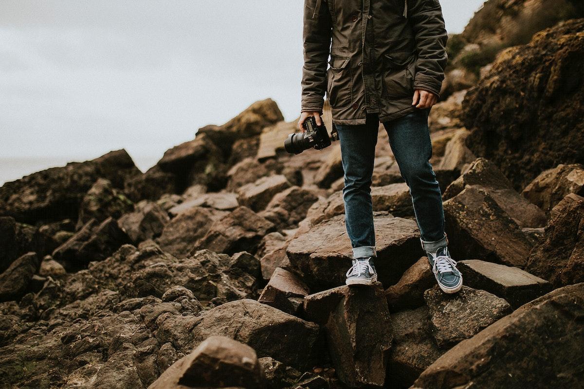 Photographer walking through rugged terrain