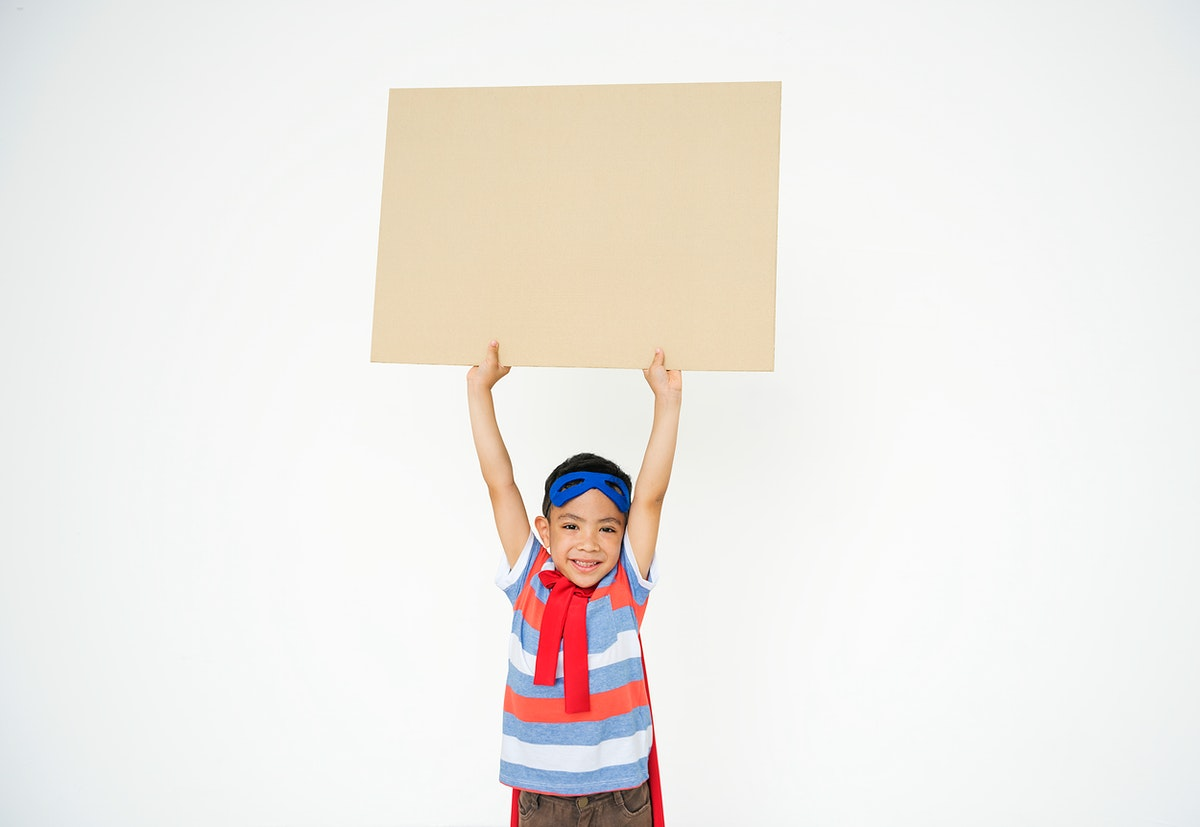 Smiling superhero kid holding up an empty placard