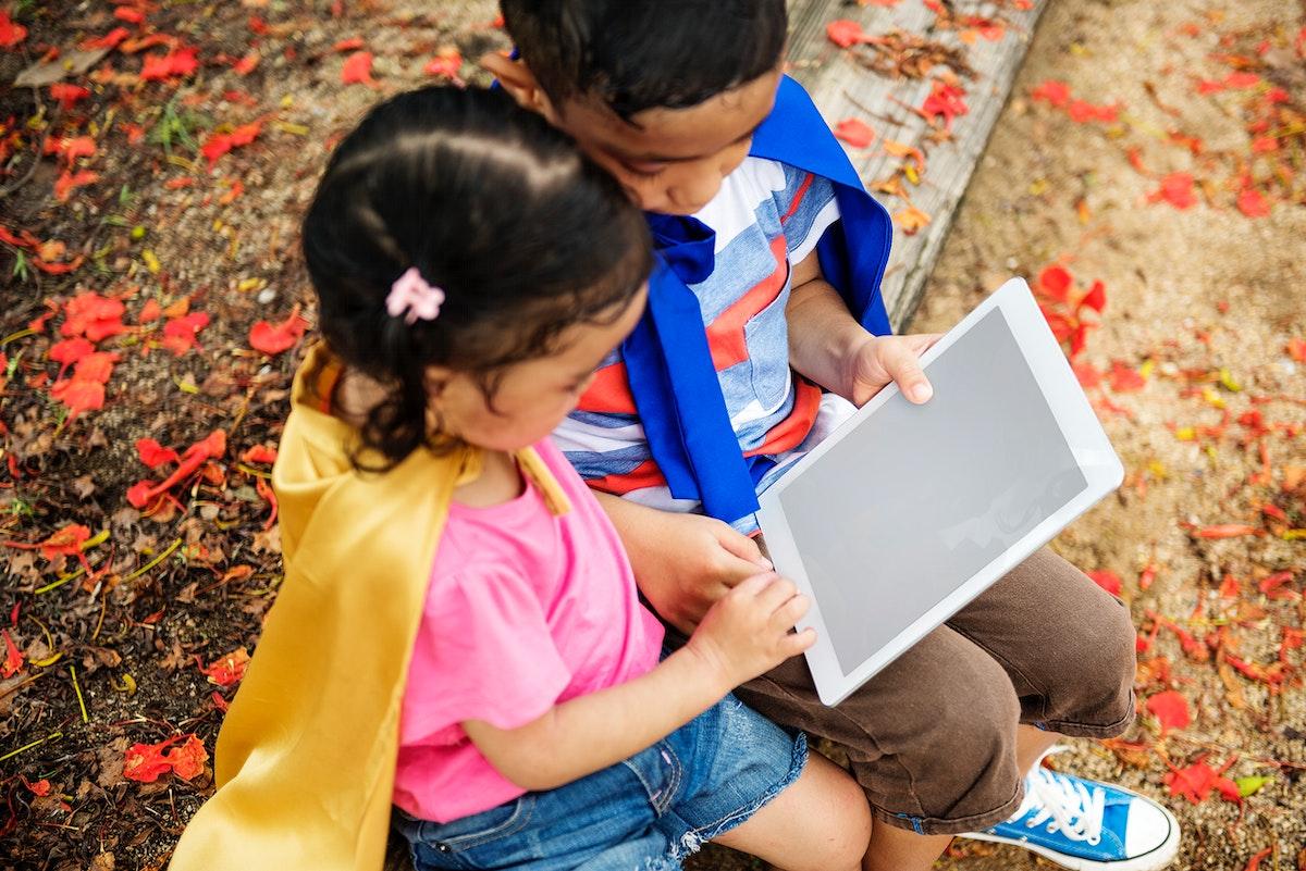 Superhero kids using an empty screen digital tablet
