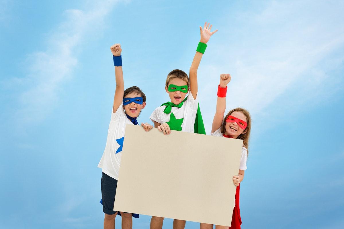 Smiling superhero kids holding an empty placard