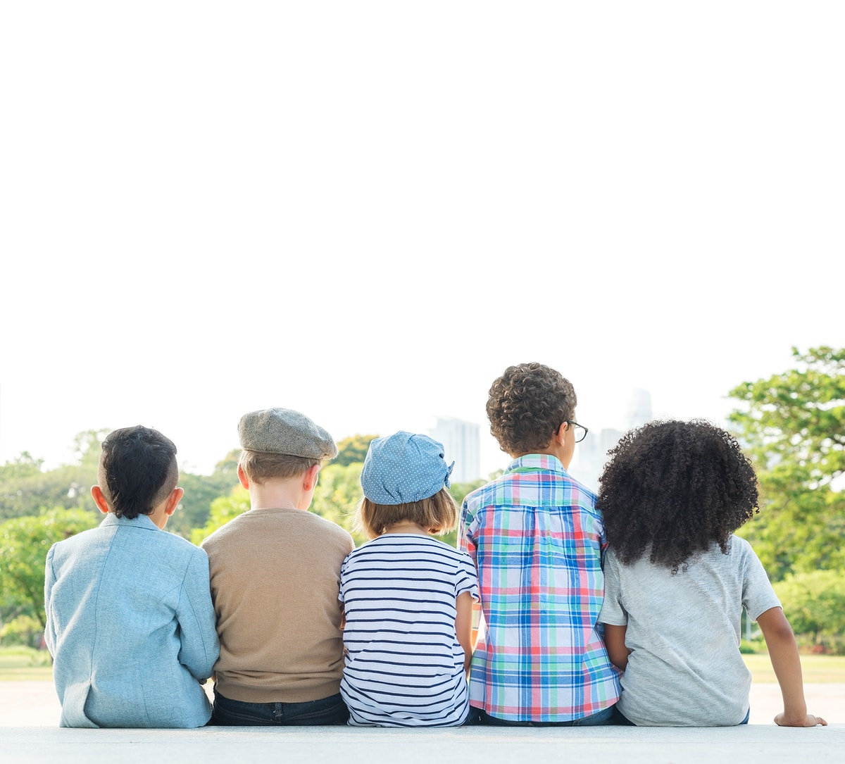 Rear view of little kids sitting together outdoors