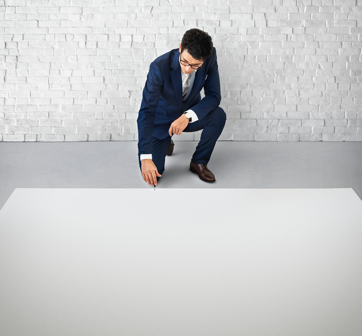 Businessman kneeling down on the floor with a big white copy space