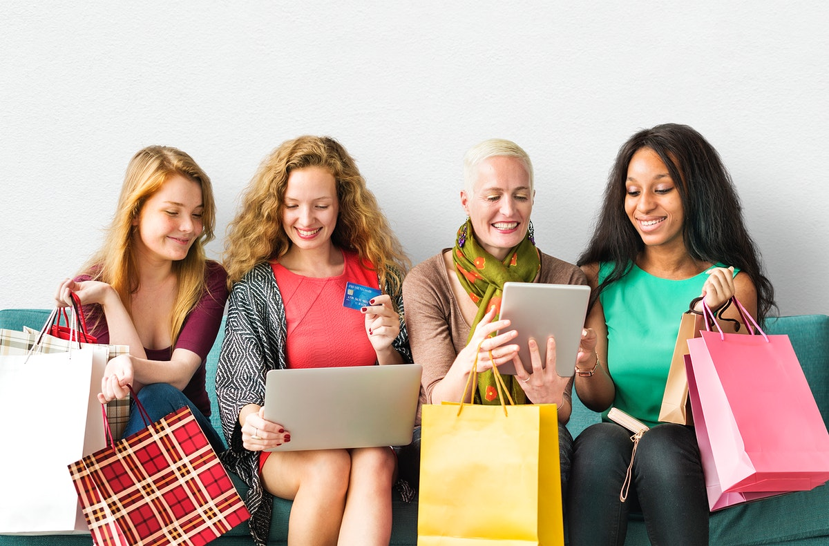 Women on digital devices with their shopping bags