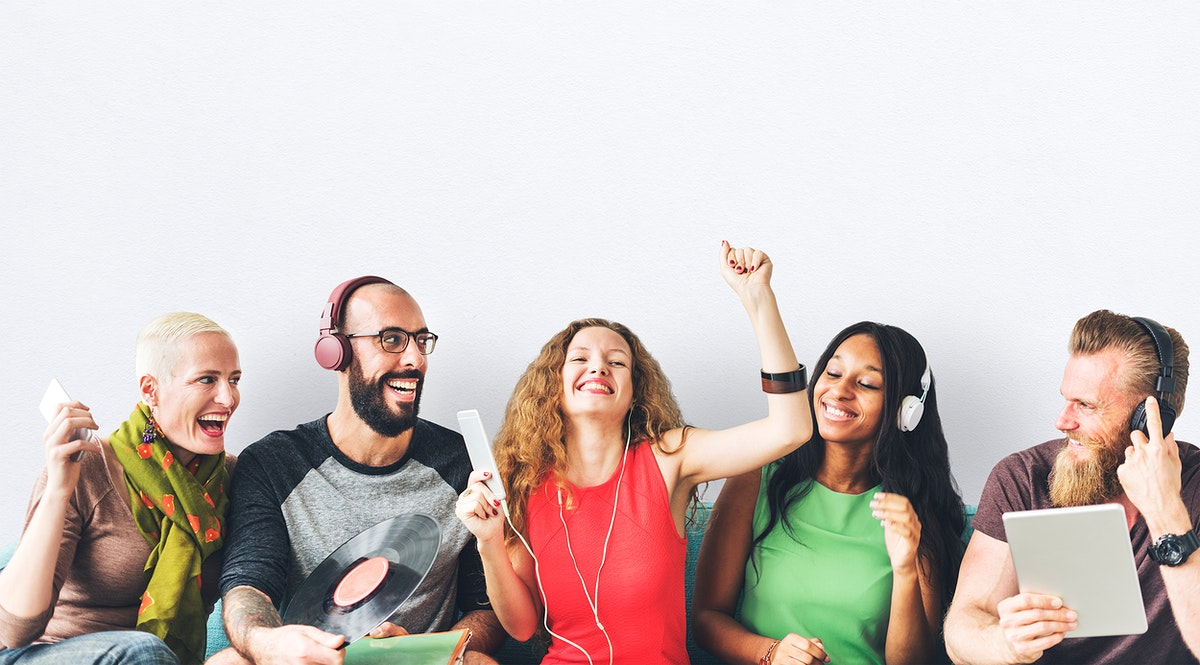 Happy group of friends sharing and listening to music