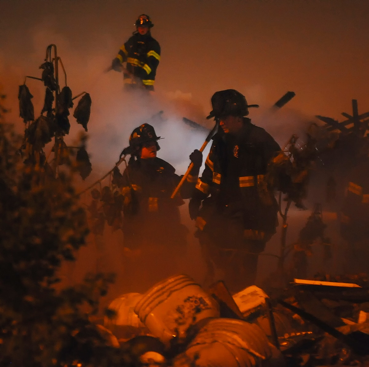 Fire Fighters assess the damage of a junk pile fire in Baltimore before overhauling the scene. Original public domain image…