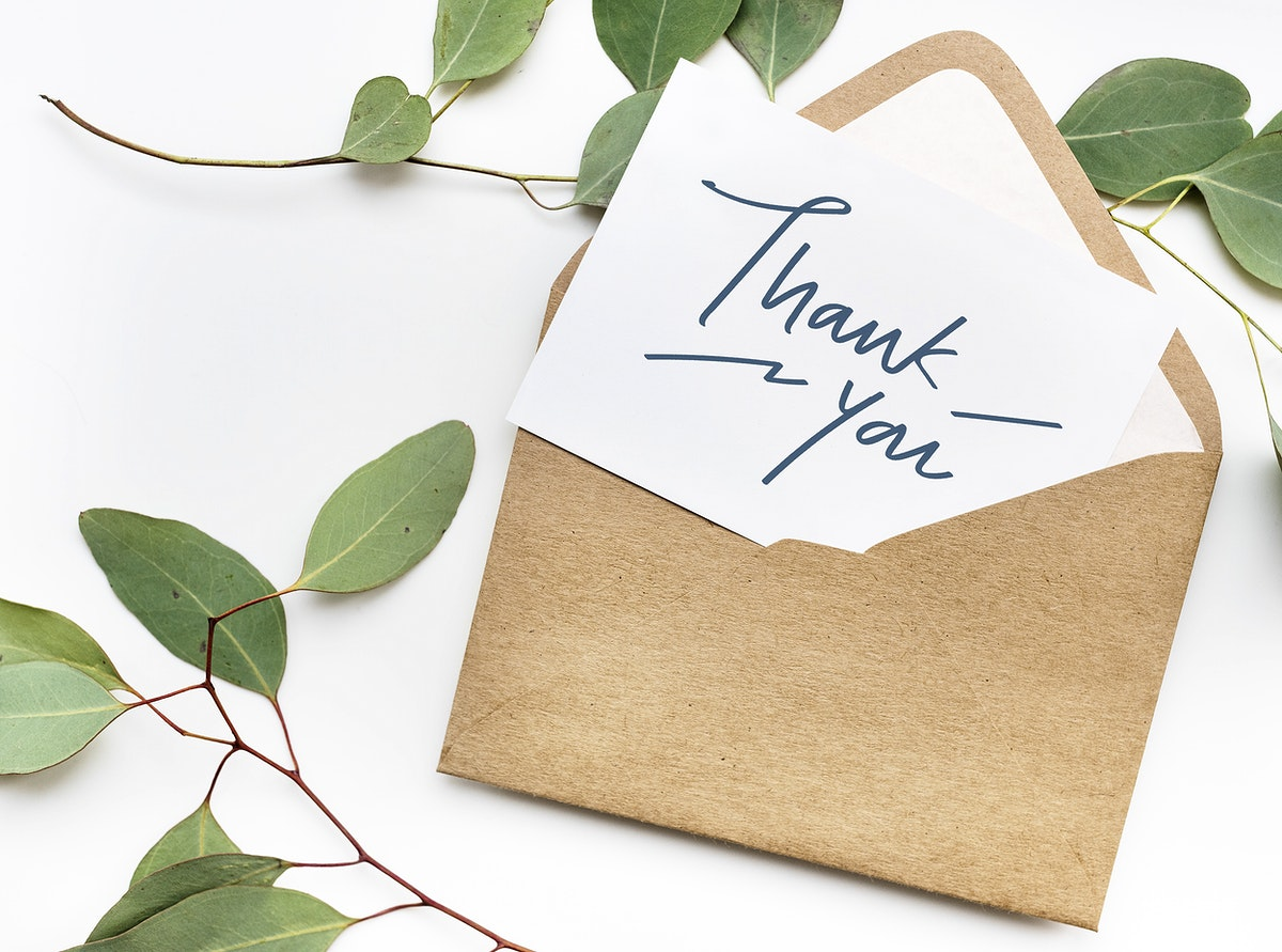 Card in an envelope mockup with leaves in the background